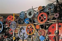 Tingueli, Jean / Jean Tinguely (Fribourg, 22 mei 1925 – Bern, 30 augustus 1991) was Zwitserse schilder en beeldhouwer. Tinguely is vooral bekend geworden door zijn kinetische kunstwerken. Hij maakte deel uit van het Nouveau Réalisme.  De invloed van het Franse dadaïsme is duidelijk voelbaar in zijn werk. De kinetische kunst heeft als voornaamste thema: de beweging in kunst. De installaties van Jean Tinguely komen zowel door motoren, de toeschouwer als automatisch in beweging, bijvoorbeeld door wind.