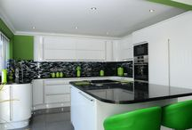 Bold colours make a bold kitchen! / Curved doors soften the streamlined contemporary design in Second Nature Porter white gloss. Neutral tones are paired with bold colours to create a focal point which naturally draws the eye in. Space is maximised with lots of pan drawers and wall larder units and the colourful bar stools make a splash of colour in a multipurpose space for the family to enjoy