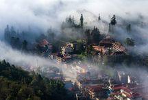 """Sapa - """"Stadt des Nebels"""" / Da sie über den Wolken liegt, wird Sapa als """"Stadt des Nebels"""" bezeichnet. Sie bietet ideale Voraussetzungen für Erholung. Das Klima ist angenehm und die Landschaften sind ein Augenschmaus, mit riesigen Reisterrassen, von Nebelschwaden bedeckten Flüssen und Wasserfällen, die in der Sonne glitzern. Sapa verfügt auch über eine vielfältige ethnische Kultur mit belebten Märkten. Ein wundervoller Ort, an den Sie nach Ihrem Besuch noch lange sehnsüchtig zurückdenken werden."""