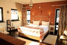 Contemplation Room 1 | Conacul Brătescu / Această cameră este decorată într-un stil rustic-romantic. Sobrietatea peretelui din cărămidă aparentă este atenuată de romantismul imprimeurilor cu flori de câmp, regăsite la tapiţeria scaunelor, la draperii şi la cuvertura de pat, dar şi la porţelanul pictat al lămpii vechi, din fier forjat. Capul de pat alb, din fier, cu elemente sinuoase, se evidenţiază prin contrastul cu peretele cărămiziu. Camera are ferestre pe trei laturi fiind foarte luminoasă şi caldă.