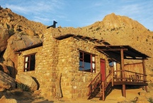 Klein-Aus Vista: Eagle's Nest Chalets / Solitude, silence, space and magnificent sunsets - these are the characteristics of the atmosphere at Eagle's Nest Chalets.  8 chalets are nestled against a mountain slope and afford unique views of the boundlessness of the desert. Each of the natural rock chalets sits between massive granite boulders and contains a bathroom, kitchenette, fireplace and private veranda. Meals are served at the Desert Horse Inn restaurant. Take-away breakfast or barbecue packs are available on request.