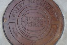 """Piston manhole covers in LCA Detroit / Some of the greatest Red Wings and Pistons players over the years are immortalized as manhole covers inside the Little Caesars Arena concourse. Has a nice, gritty """"Hollywood Walk of Fame"""" style to it.  Dave Bing and his No. 21 on one cover. The former mayor of Detroit played for the Pistons from 1966 to 1978. He was inducted into the Basketball Hall of Fame in 1990."""