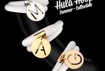 Hula Hoop / Bracciale in caucciù bianco a doppio giro, arricchiti da ciondoli con lettera traforata in oro giallo, oro bianco e oro rosè.