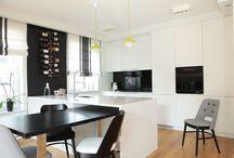 Minimalistyczne mieszkanie / Minimalistyczne wnętrze skomponowano w 3 kolorach: białym, czarnym i szarym. Ze względu na liczną zieleń znajdującą się dookoła dopełnienie stanowi kolor zielony, wyeksponowany w dodatkach. Wnętrze zostało ocieplone przez zastosowanie naturalnej, dębowej podłogi. Architekt połączył kuchnię z salonem tworząc dużą otwartą przestrzeń, tym samym kuchnia z funkcjonalną wyspą i wysuwanym stołem stała się miejscem integracji rodzinnej.