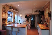 Exposed Brick Kitchen with Classic Filament Lights, Rustic Cupboards & Exposed Floor / Open brick kitchen with oiled walnut worktops, Thomas Kent clock, rustic chopping boards, vintage cupboards & original 1940's floor tiling