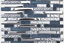 Мозаика стеклянная / Стекло – самый недорогой и популярный материал. Он неприхотлив в уходе, износостойкий, абсолютно не поглощает влагу. Кроме того, стеклянная мозаика выглядит очень эффектно – шикарное разнообразие цветов и форм позволяют «творить» разнообразные интерьерные решения.  Кстати, мозаику, в отличии от крупноформатной плитки, можно применять на непростых на первый взгляд выпуклых и вогнутых поверхностях.