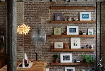 living in a loft. / red brick walls, huge window, wood beams under the tall tall  ceiling, bookcase covering the entire wall, huge concrete fireplace, leather bauhaus-inspired sofa and industrial chic. if i ever have a bazillion dollar house, my spacious lofty living room will look just like that.