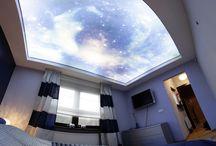 Sufit napinany w sypialni z nadrukiem nieba podświetlony taśmami LED. / W galerii przedstawiamy zdjęcia z realizacji projektu sypialni, w której sufit napinany z nadrukiem nieba został podświetlony taśmami LED o barwie białej zimnej.