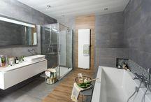 Nordic Line badkamer / De sfeer van Scandinavië gevangen in een badkamer, dát is Nordic Line. De warmte van het hout, het kleurenpalet in wit, grijs en pastel, de schittering van de mozaïektegels… Elk detail voelt heel natuurlijk en versterkt de balans. Ook planten kunt u op een creatieve manier in deze badkamer als stijlelement toepassen. In de Nordic Line badkamer valt de stress van alledag vanzelf van u af.