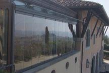 Terrazzo in Toscana / Veranda in Toscana. Vista sull'entroterra.  Realizzata con vetrata Giemme System. Nelle abitazioni private rappresenta un ottimo sistema per terrazze, verande, balconi, porticati,  gazebo e giardini d'inverno: offre una soluzione flessibile e allo stesso tempo efficace contro agenti atmosferici.  Si apre a pacchetto laterale e non ha limiti in senso orizzontale, dato che si tratta di un sistema modulare.