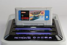 Retron 5 / Play thousands of retro video games with this all-in-one 'Retron 5' retro games console. Included retro games cartridge/game slots: Nintendo NES, SNES (Super Nintendo), GameBoy Advance (GBA), SEGA Genesis / SEGA Mega Drive, Nintendo Famicom, Super Famicom, Gameboy Colour and Game Boy!   • Region FREE! (play your PAL/NTSC cartridges with ease)  • HD upscaling up to 720p with 4:3 or 16:9 ratio select  • Save/Load your progress