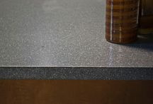 Karma Stone / KarmaStone is a new collection of manufactured concrete slabs. It is a precast material made of 70% recycled natural stone and a Portland cement binder.  It is considered a cement or concrete surface. While all Karma StoneStone comes in 3 base colors the surface can be customized to a number of colors with the addition of KaraStone Topical Surface. It can be used as kitchen countertops, vanities or even table tops.