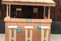 Lounge bar / Lounge bar gemaakt van douglas hout met rieten dak. Rondom van lichtslangen voorzien voor de verlichting. In de bar staat een horeca ijskast met glazen deur en een biertender.