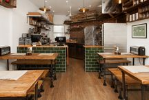 Urban Industrial Interior inspiration and design idea / Urban Industrial Interior and design insperation with wooden dining table and bench, dark iron legs and copper pendant lamps, green wall tiles, wooden units and open shelves