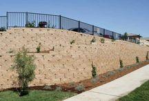Støttemur REK / REK finnes med rett og buet framside. Blokkens løsning er utformet for å passe høye støttemurskonstruksjoner og med geoarmering kan du i prinsippet bygge så høy mur du ønsker.  Muren er først og fremst tiltenkt større konstruksjoner i offentlige miljøer. På plasser der man vil forene teknisk konstruksjon med estetikk, er REK en svært kostnadseffektiv løsning.  Med REK kan man variere høyder, radier og terrasseringer i det uendelige.