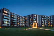 RAVN_HavneBO / HavneBo ligger på Vejle havns nye boligområde. Området rummer en ny stor lystbådehavn, fjord med muligheder for sejlsport og et stort grønt parkrum.  Konceptet er enkelt og ligefrem: Bebyggelsen er formet som en åben karré med en knækket bygningskrop, der definerer gaderummet på den ene side og åbner op mod parkrummet og den grønne kile på den anden.