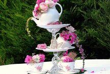 Wedding decor & dishes / Kaikki mieluiten mahdollisimman vanhanaikaisen tyylistä tai pelkistettyä, ei modernia. Mieluiten kuvioidut tai yksiväriset pastellisävyiset, vaaleat tai valkoiset teekupit ja aluslautaset. Kaikilla voi olla erilaiset keskenään jos ei ole mahdollista saada samanlaisia. Samantyyliset teekannut tai hopeiset/metalliset tai lasiset. Kerrostarjottimet kuppien tyyliset tai hopeiset/metalliset. Koristeena teekannuja ja/tai teekuppeja ja/tai kerrostarjottimia joissa pastellisävyisiä ja valkoisia kukkia.