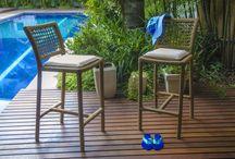 Linha Guaylandia / A linha Guaylandia é um conjunto composto por mesa retangular para 6 lugares (1,65x100 cm) ou mesa quadrada para 4 lugares (100x100cm) e banquetas. Suas peças são trançadas manualmente em fibra sintética, com detalhes em madeira que é tratada com produtos específicos para maior durabilidade às adversidades do tempo. A cadeira tem versão com e sem braço e possui estofamento para maior conforto.