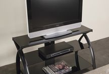 Calico Designs Modern Metal & Glass TV Stands by Studio Designs / These TV stands offer sleek lines are are made of durable metal and glass.  These TV stands are available in silver and black and come in a variety of sizes.