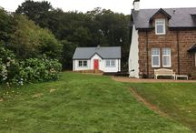 Two Bedroom Bespoke Wee House - Isle of Arran 55M2 / This magnificent Wee House on the Isle of Arran was commissioned to have 2 beds, shower room and open plan living area.  The colours are swedish white on the timber wood, red on the front door with a dark grey corrugated roof.