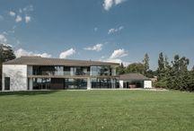 RAVN_Villa H / Villaen er udformet med tre fløje, hver med et asymmetrisk skrånende tag, der tilfører byggeriet et skulpturelt udtryk. Mod nord dannes et gårdrum med adgang til hovedbygning, gæstefløj og carporte.