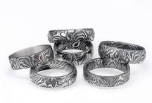 Damascus Stainless Steel Mokume / Damascus stainless steel mokume rings and jewelry are individually crafted to order just for you. Each item is hand carved and then etched to produce these beautiful patterns. Damascus steel rings can be ordered with inlayed strips of precious metals, or they can be mounted in a channel of precious metal or titanium if you desire.  Upon request stainless steel damascus can be blackened to produce a striking two tone design.