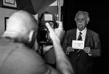 George Bizos - Behind the Scenes / Bizos stands facing the camera with hands outstretched holding a handwritten note that reads 'if needs be'. At the request of Bizos, Mandela inserted these three simple words into his Rivonia Trial speech from the dock in 1964. The inclusion of these three words is said to be the difference between life and death for the defendants of the Rivonia Trial.