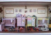 Quadro Personalizado para Maternidade / Tamanho: 42L x 14P x 21H Diorama laborado em MDF com detalhes laterais em gesso e acabamento branco. Peças recicladas, madeira balsa, palitos de dente, bijuterias, mini brinquedos infantis, tecidos, criação e desenvolvimento para impressões de quadros, revistas, capas de livros, fotos particulares, rótulos dos produtos e papel de parede com border em papel couchê e biscuit. Uso de vidro frontal embutido em canaleta para proteção.