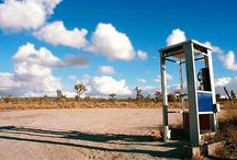 Mojave Phone Booth / The hand cranked payphone, known to locals as the Cima Dome phone, was installed in the Mojave Desert in  the 1960s, along a dirt, washboard road called the Aikins Mine Road.  It provided local ranchers and cinder miners with the only phone service for miles around.  Around 1997, a person had noticed a phone handset symbol on a map.  Investigating, the individual actually found the phone booth, just like on the map!  PacBell clandestinely removed the phone booth on May 17, 2000. / by Michelle Hansen