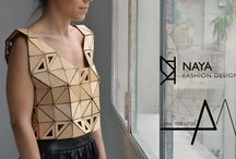 wooden clothes / Anna Moraitou, Vaya Nikolakopoulou & Nara Papakaliati worked together to create a collection of wooden clothes and accessories. Influenced by the work of fashion designers like Paco Rabanne and architects like I.M. Pei, they use the isosceles triangle, an elementary geometric shape that provides strength and stability in structure. Several triangles are connected together and follow the curves of the body, so as to create a functional architectural wearable construction.