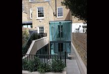 Project: Paultons Square / Double height facade glass going into basement to a Grade II Listed townhouse. Minimally framed sliding glass doors and frameless structural glass make up the double height extension