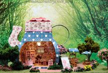 """Quarter Scale Miniature, The Tea Room /  I made the teapot from cardstock, and the flower, on the top, from printer paper. I also printed the teapot wallpaper and outside design with my printer. The teapot is a template from My Time Made Easy,LLC. I resized the template to fit the quarter scale furnishings. The Teapot is 5"""" square x 5.75"""" T. It sets on a 13.5"""" L X 9"""" W board."""