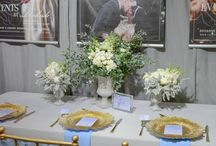 Corporate Styling, Landing at Dockside / A colour palette of dove grey, warm white accented by gold hues, brought this Queensland Brides Wedding & Honeymoon Exhibition booth to life for the Landing at Dockside. Perfectly capturing the effortless style of this venue with the soft gold Tiffany Chairs, complimented by custom designed powder blue watercolour menus, place cards & table number. Youtube: https://www.youtube.com/watch?v=tcGCd73cluA&feature=youtu.be