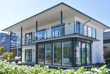 """Modernes Wohnen ohne Kompromisse / Besuchen Sie uns auf der """"Home Expo"""" im schweizerischen Suhr und entdecken Sie ein Haus, das mit moderner Architektur und einem freiheitsliebenden Wohnkonzept den Ansprüchen der Zeit gerecht wird. Unter dem Walmdach unseres rechteckig geschnittenen Ausstellungshauses verbergen sich zwei Vollgeschosse und damit mehr als 165 Quadratmeter Wohnfläche. Optisch beeindruckt das Haus mit klaren Linien und vielen Fensterflächen."""