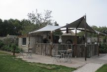 """Pig On The Beach Hotel / The remit here was to design and instal a bespoke tensile sail to provide all weather seasonal cover ( April – October) over the Pizza Oven & Bar area. The Pizza bar was wrapped around the dry stone wall which encloses a market garden used by the Hotel for fresh produce.   The design is based on our """" Schooner """" concept of varnished laminated timber masts combined with spars and tensioned cables to absorb the sail tension forces. Finished with stainless steel mirror polished fittings."""