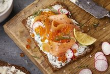 Smorrebrod / Danish open-faced sandwiches. Start with dense rye or pumpernickel, spread thick with butter. Top with meat, fish or cheese and garnish beautifully.