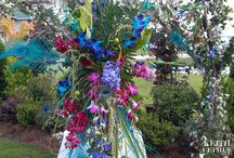 A wedding of Peacock Feathers, Teal, Blue and Fuschia flowers / The bride wanted her colors to pop with teal, royal blue and fuschia, and she wanted peacock feathers. We used teal and fuschia dendrobium orchids, fuschia stock, fuschia carnations, green button mums, magenta mums, lavendar, and hanging amaranthus. We also created a peacock out of flowers, which sat underneath a life-sized willow tree in the foyer. The peacock was made of the same floral materials as all the other wedding flowers.