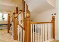 Little Gate Staircase / This is a very impressive double-winder staircase manufactured from both American white oak and softwood. To enhance the modern style of the property, 150mm American white oak newel posts with elliptical ball caps have been used along with a D-end feature step on the entry of the stairs. The 35mm stop-chamfered spindles have been painted white. Our customer decided to carpet the stairs, so softwood treads and risers were used.