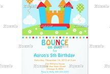 Boy Bounce House Birthday Party / This collection features a bouncy castle, bounce house situated on a hill with daisy flowers, two balloons and a bright blue sky with clouds. The colour palette consists of blue, orange, red and green. Stripe background.