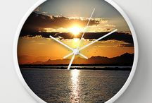 "WallClocks / Available in natural wood, black or white frames, our 10"" diameter unique Wall Clocks feature a high-impact plexiglass crystal face and a backside hook for easy hanging. Choose black or white hands to match your wall clock frame and art design choice. Clock sits 1.75"" deep and requires 1 AA battery (not included)."