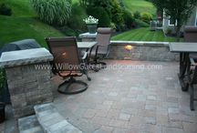 West Chester Raised Two Tier Patio / This raised patio project involved removing a great deal of fill and replacing with clean gravel in order to safely build a raised patio.  Materials used: Techo-Bloc Mini Creta walls & pillars in Chestnut Brown, York pillar caps in Chocolate Brown, Hera pavers in Autumn Red, and bordered with Chocolate Brown.  Integral LED lighting was installed in the walls & steps.