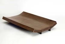 SPLIT / Split è un contenitore realizzato in legno massello curvato, ottenuto partendo da una tavola piana rettangolare debitamente fresata alle estremità dei lati maggiori per tutta la loro lunghezza. Le fresature sezionano le fibre del legno per agevolare la piegatura dei lati della tavola, ottenibile con semplici mezzi meccanici manuali.