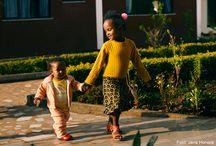 Livet i en SOS-børneby / I en SOS-børneby får forældreløse og udsatte børn et trygt hjem for resten af deres barndom. En børneby består af 10-15 familiehuse, og i hvert hus bor en SOS-mor sammen med 6-10 børn. SOS-moren tager sig af børnene som var de hendes egne; hun sender dem i skole om morgenen, laver mad, putter og kysser dem godnat og passer på dem, når de er syge.  Lige nu vokser 82.300 forældreløse og udsatte børn og unge op i mere end 500 SOS-børnebyer verden over.