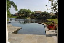 Pool Fireside Design / This custom shaped pool designed and built by 5 Star Outdoor Design looks as if it runs right into the lake because of its zero edge side. If you step down from the pool patio you see a fire pit actually built into one side of the pool. As you walk further around to the front of this Ponte Vedra Beach, FL home you see uniquely placed pavers and a beautifully stacked stone wall that help show off the grand pillars of this truly unique home.