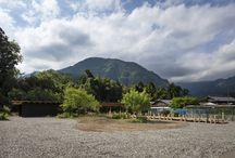 はなれ hanare(Guest house) / [もてなしの心とゆずで人をつなぐゲストハウス]徳島県の木頭で働きながらアマチュア・カメラマンとして多くの人に愛された中野健吉さん。病に倒れたが、妻のみね子さんに「したいことをしたらいい」という遺言を残した。みね子さんはそれに従って健吉さんの写真を展示する「ケンズ ギャラリー カフェ」を運営、音楽イベントなども開いている。が、このカフェや、地元の名産である木頭ゆずを目当てに遠方から来てくれるお客さんがいても泊まるところがなく、残念に思っていた。そこで作られたのが、このゲストハウスだ。   建物は広い敷地を活かしてエントランスから奥に入ったところに配置。間に木で架け橋のようなアプローチを作った。日常から非日常へ、現実から非現実へと渡っていくようなイメージだ。建物周辺には砂利を敷き、その周りは自然のままにして豊かな緑を身近に感じられるようにしている。