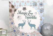 Dovecraft Magic and Sparkle / Enter into a wintry world filled with Christmas charm in Dovecraft's  Premium Magic & Sparkle papercraft collection. Peer inside the paper pad to find pastel pink, blue and beige pages decorated with intricate snowflakes, reindeer, The coordinating embellishments include sequins, buttons, glitter dots, glitter frames, foil stickers and more. Christmas trees, stars and other festive patterns.