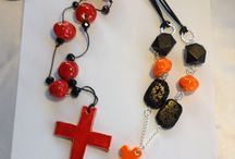 Orange ceramic cross and beads, with black lava flat oval beads and two faceted black wooden beads strung on silver and black leather adjustable ties