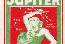 Jupiter of Mád / The thick paper has a rough off-white high-fiber content surface. There is a reminiscent of copperplate two-coloured graphic made with unknown technology on the smoother surface, where the paper gives the third shade. The line 'Jupiter' is inscribed in a lineared square red box. A shape of a bearded man appears holding lightning like arrows in his fist over his head in the green brand within the red box.
