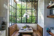 Cocina con ventanal de hierro negro y vidrio con mesa de madera y ekbank