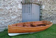 Wooden Clinker Dinghies / Stirling and Son are the leading builders of traditional clinker dinghies.  Built of mahogany on oak they come with a pair of leathered sweeps, a pair of bronze rowlocks, a brass ringbolt in stem and sternpost, a brass keelband and brass bilge rubbing bands, mahogany capping rails and fitted sole boards. The standard finish is an oiled interior, with gloss varnish topsides, capping, gunwhales, thwarts and knees, a gold inlaid cove line and carved scroll work and paint below the waterline.